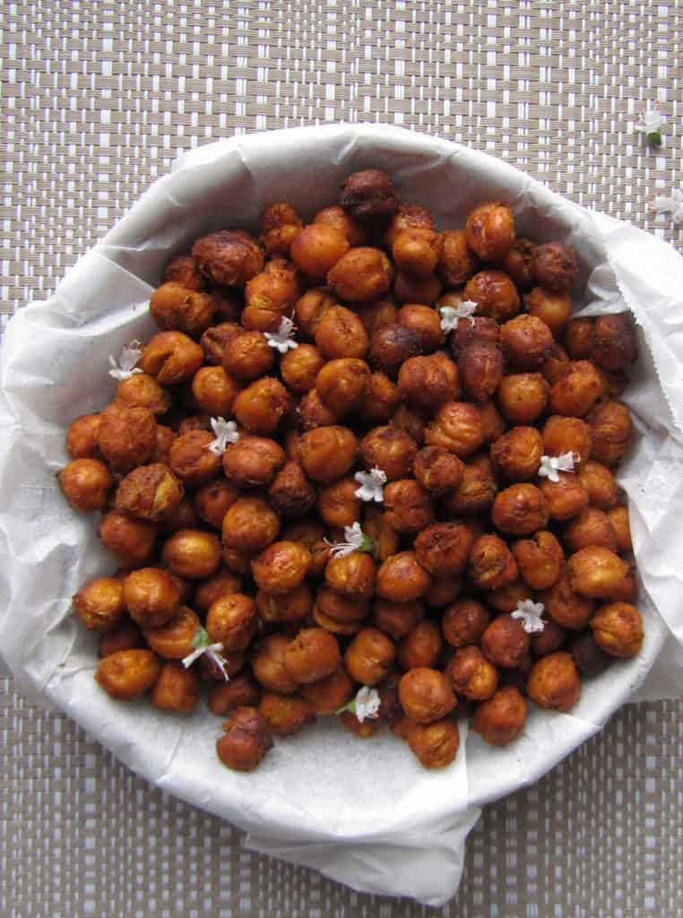Roasted chickpeas garnished with white edible flowers