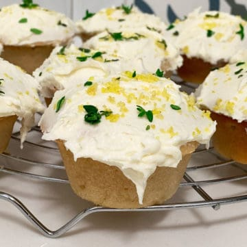 Lemon and thyme cupcakes sitting on a wire rack