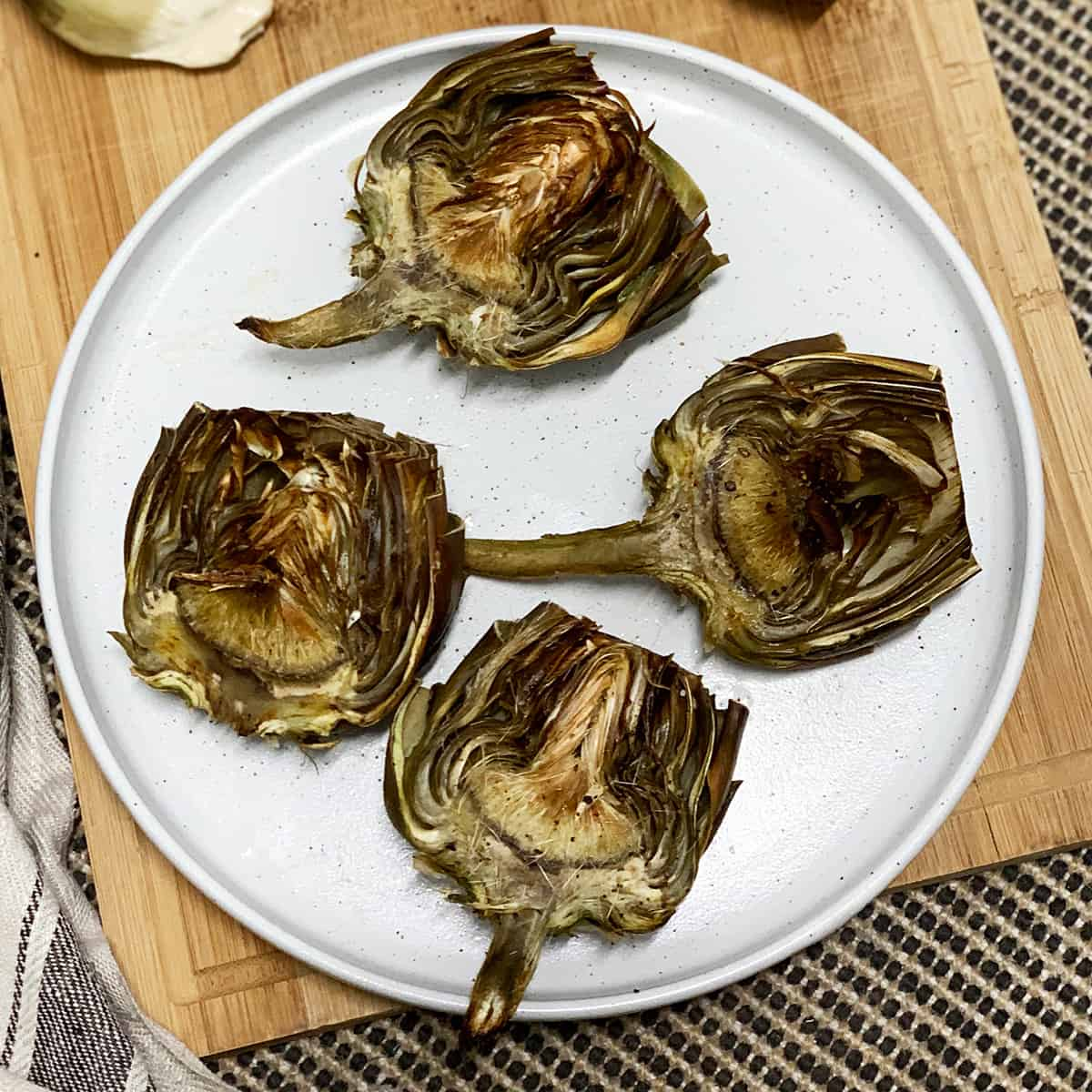 A plate serving four roasted artichokes