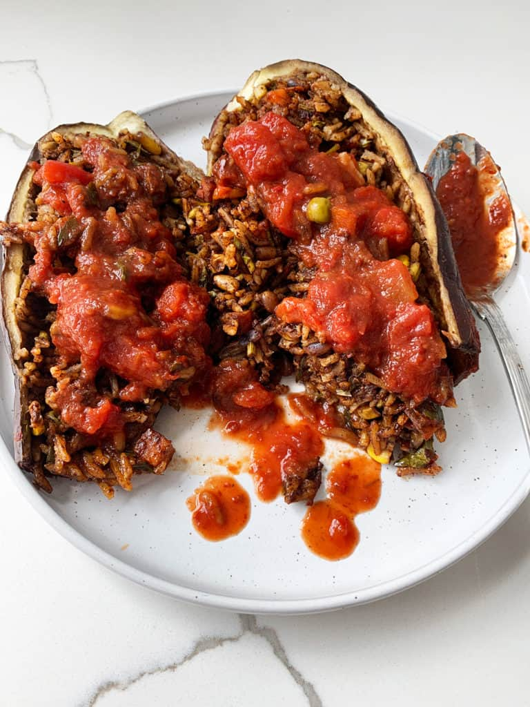 Cooked stuffed eggplant cut in half to show content of rice, pine nuts and vegetables
