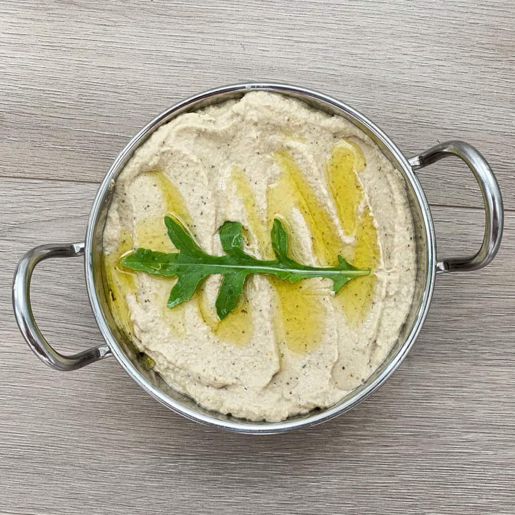 Lebanese Baba Ghanouj dip with Mint served in a steel bowl and garnished with olive oil and rocket