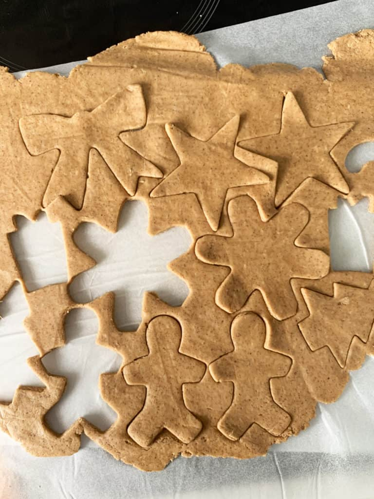 Rolled out ginger bread cookie dough thats been cut out into shapes; xmas trees, stockings, gingerbread men