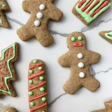 Gluten free gingerbread cookie in the shape of men, stockings, presents and christmas tree on a marble countertop