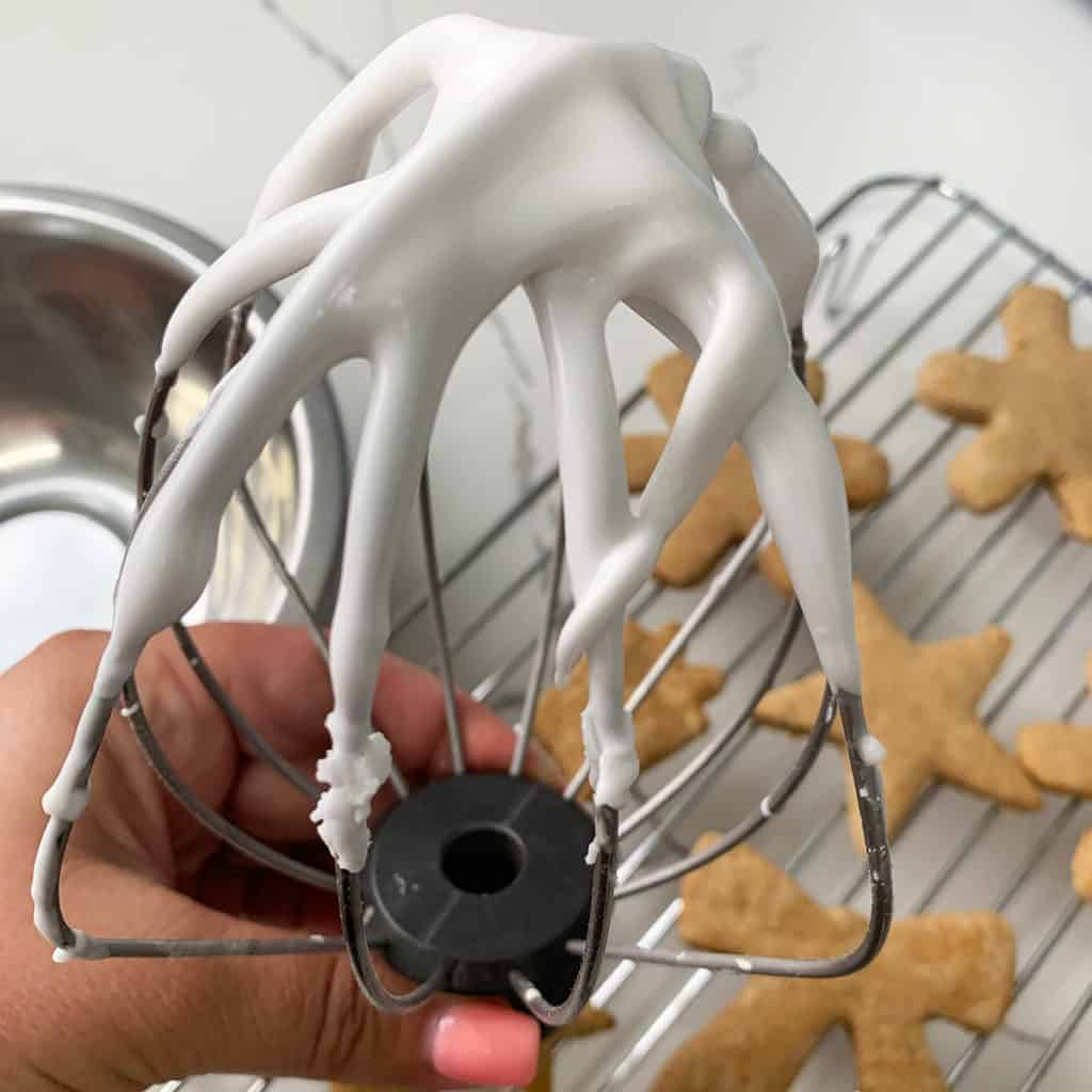 A held up whisk covered in vegan royal icing with ginger bread cookies in the background