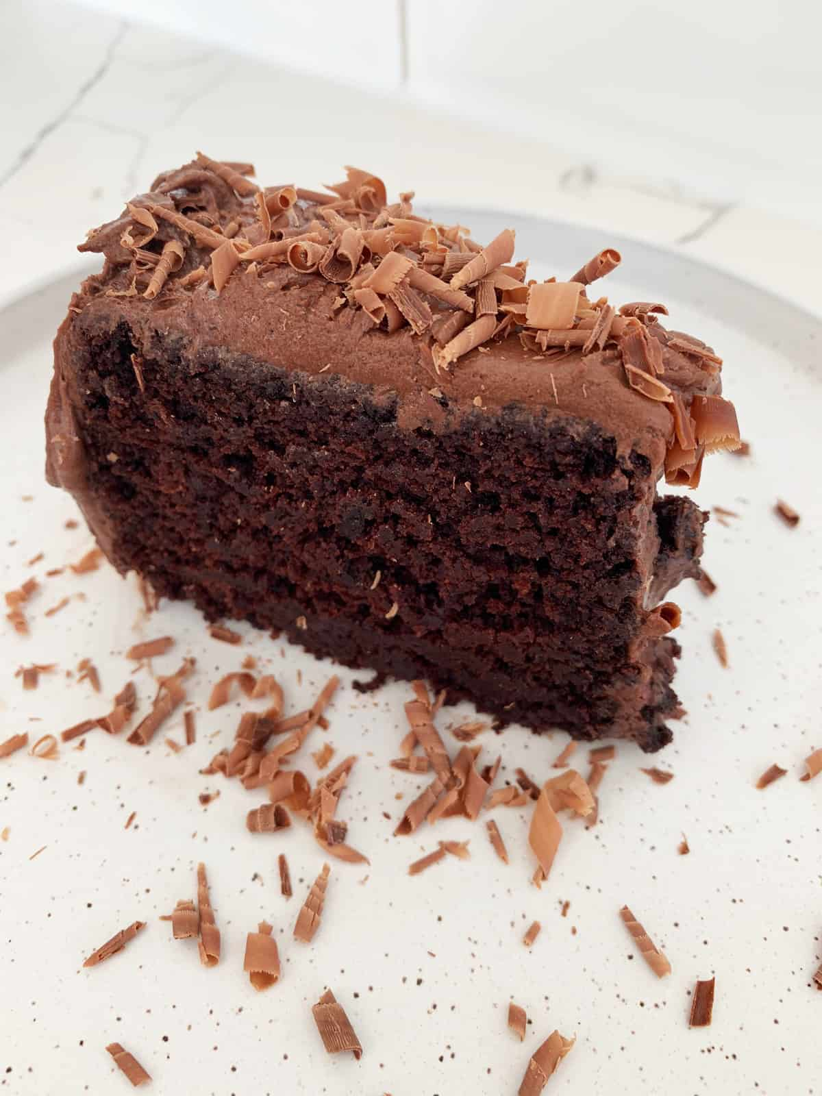 Chocolate Zucchini Cake Slice on a white plate with chocolate shavings as garnish on scattered on plate