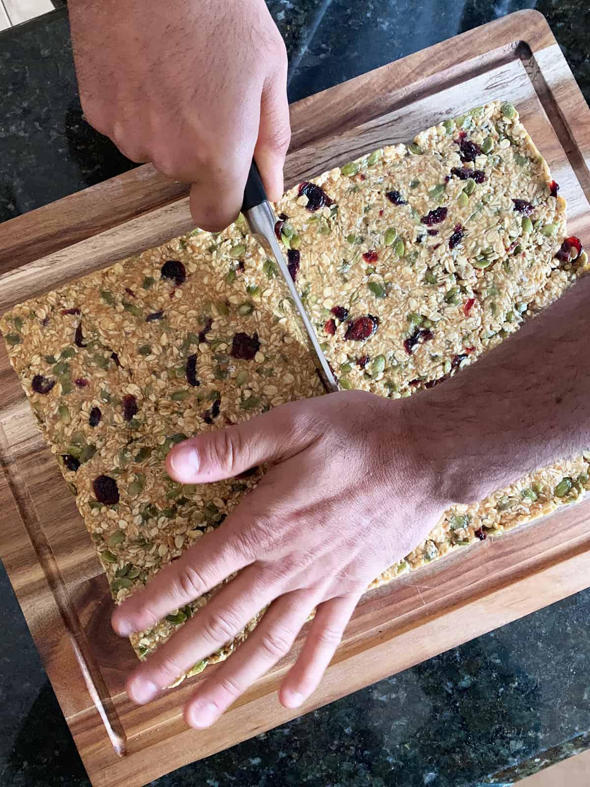 male hand cutting a slab of no bake granola bars