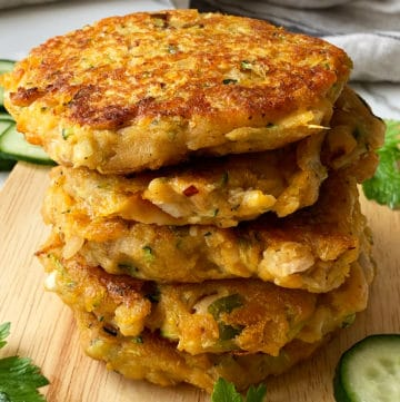 A stack of 5 sweet potato & zucchini fritters on a chopping board with cucumber slices on the sides