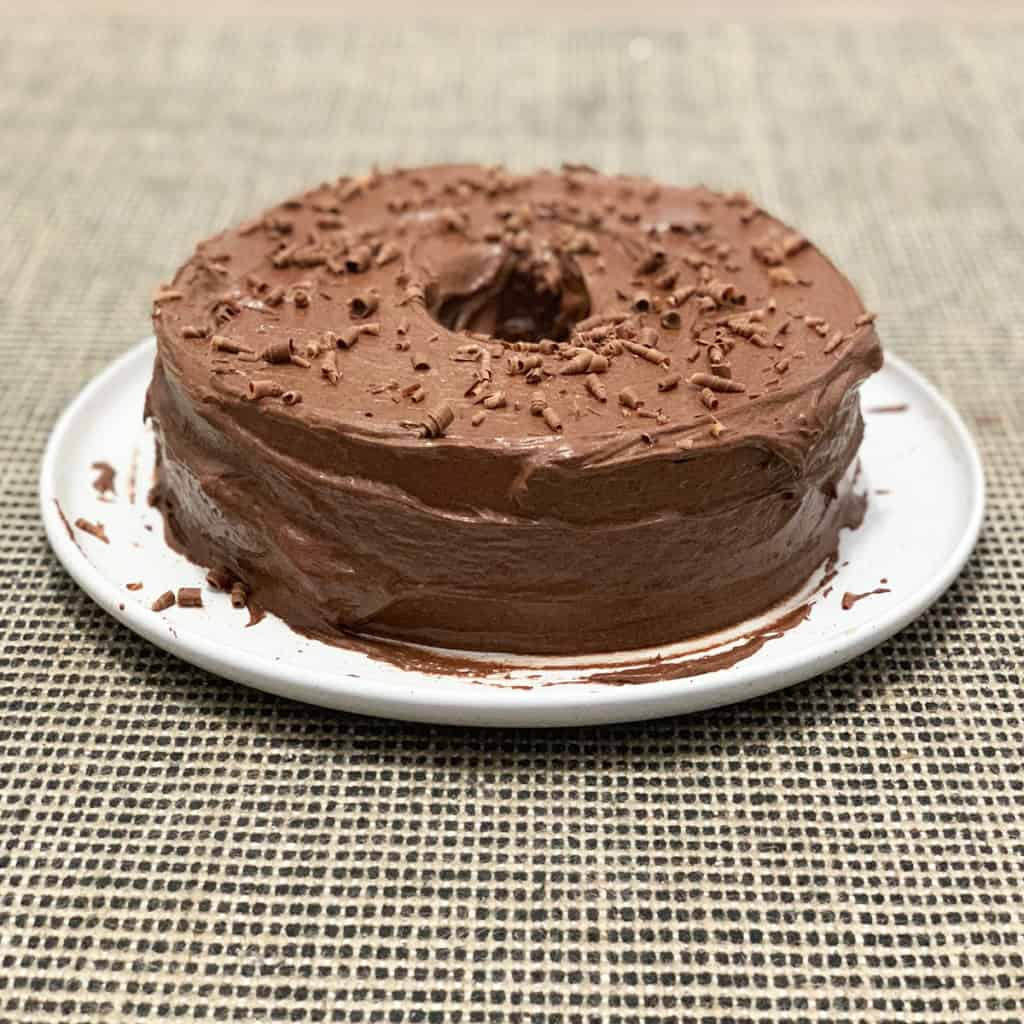 Whole chocolate zucchini cake on a white plate