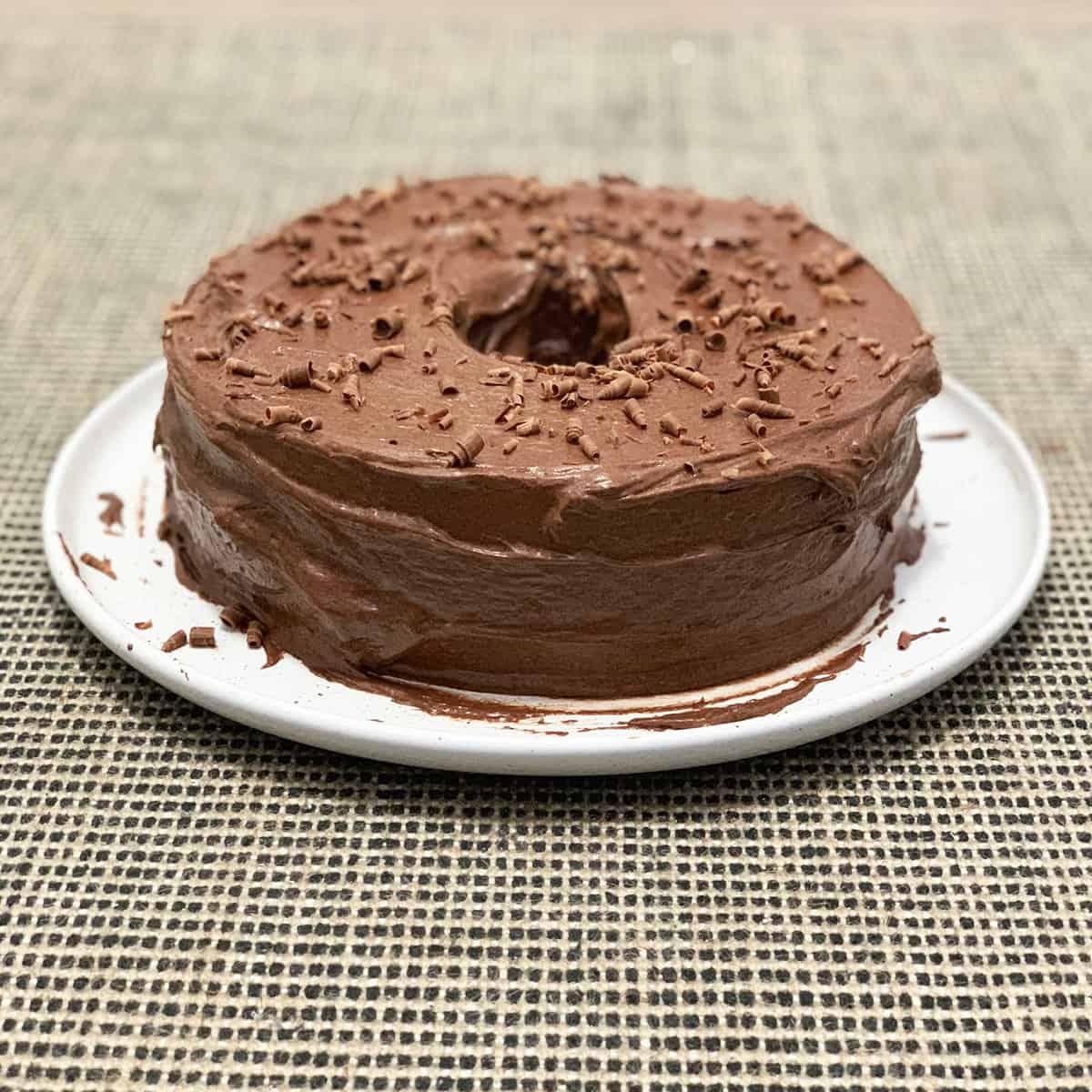 Whole chocolate zucchini cake on a white plate