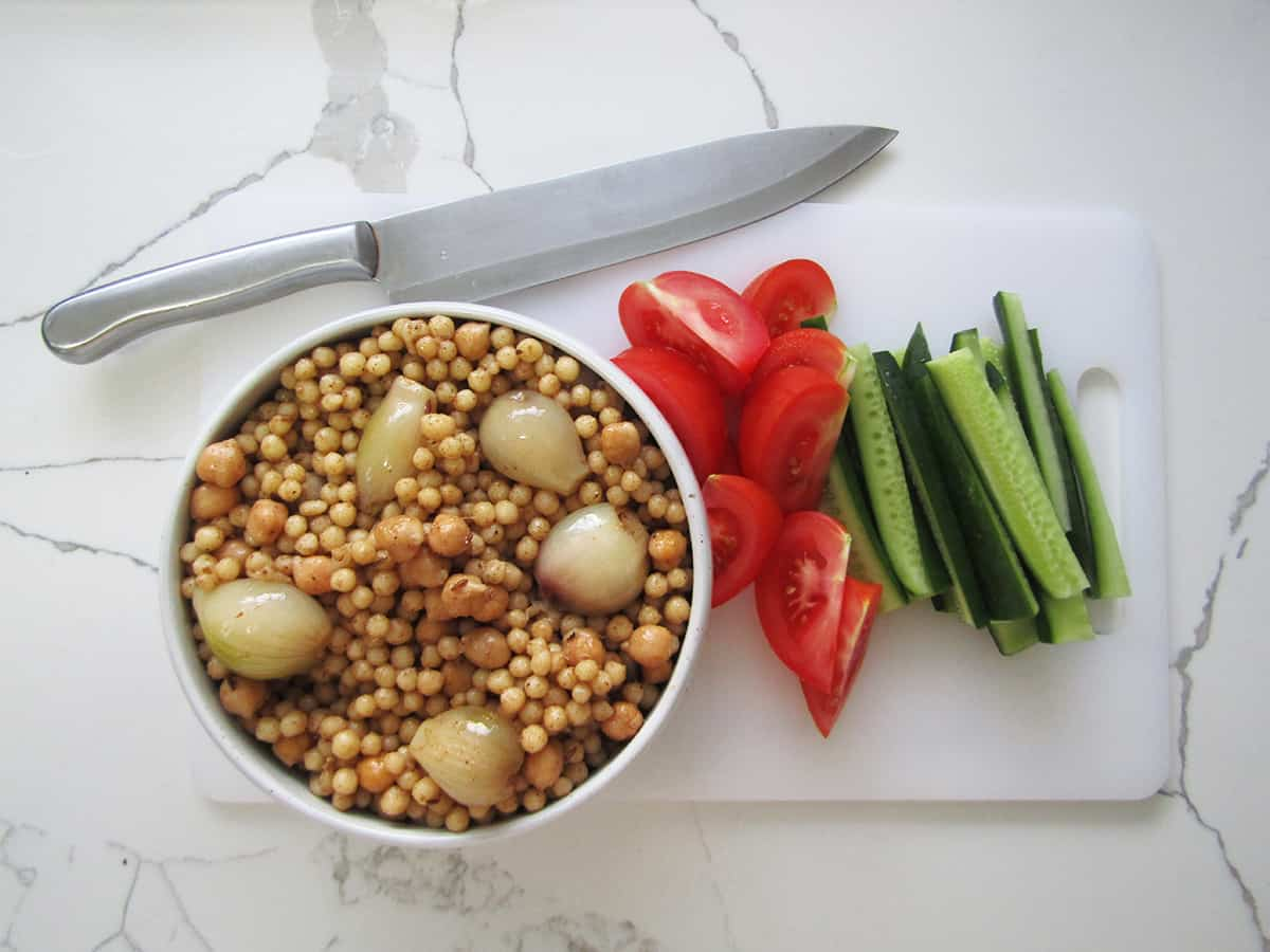Mograbieh, pearl couscous in a bowl on a chopping board with cut up tomato and cucumber with a knife on the side