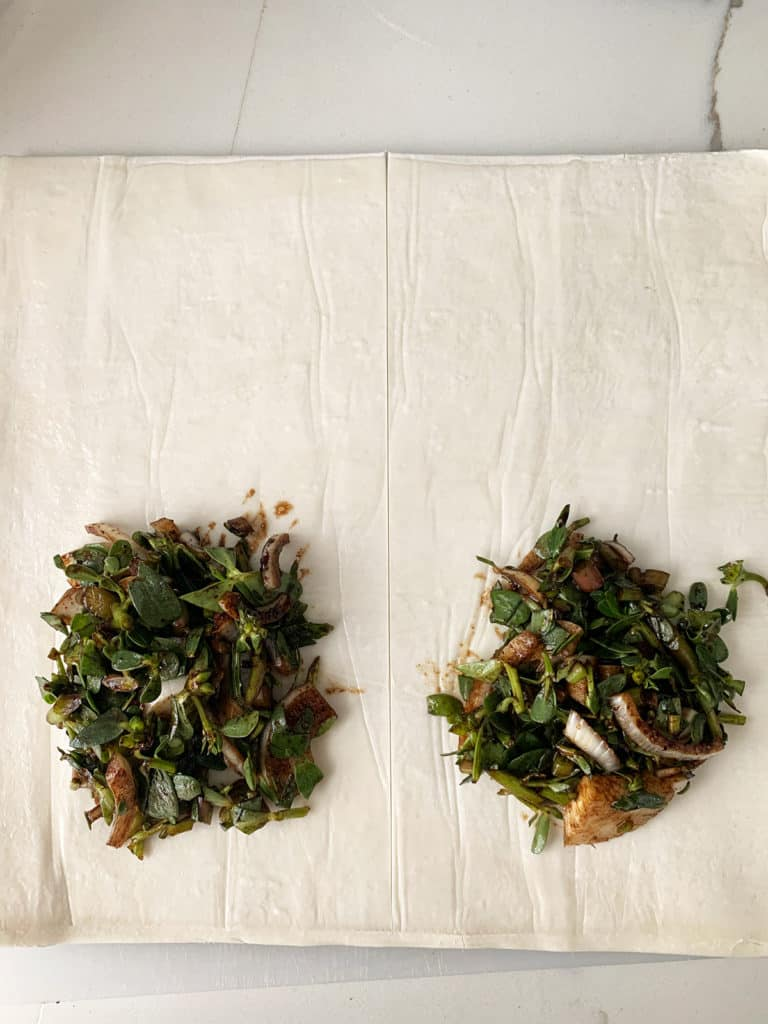 Purslane/bakleh filling placed on one edge of puff pastry sheet