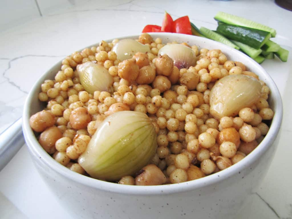 Lebanese Pearl Cous Cous in a white bowl with a side of cucumber and tomato in the background