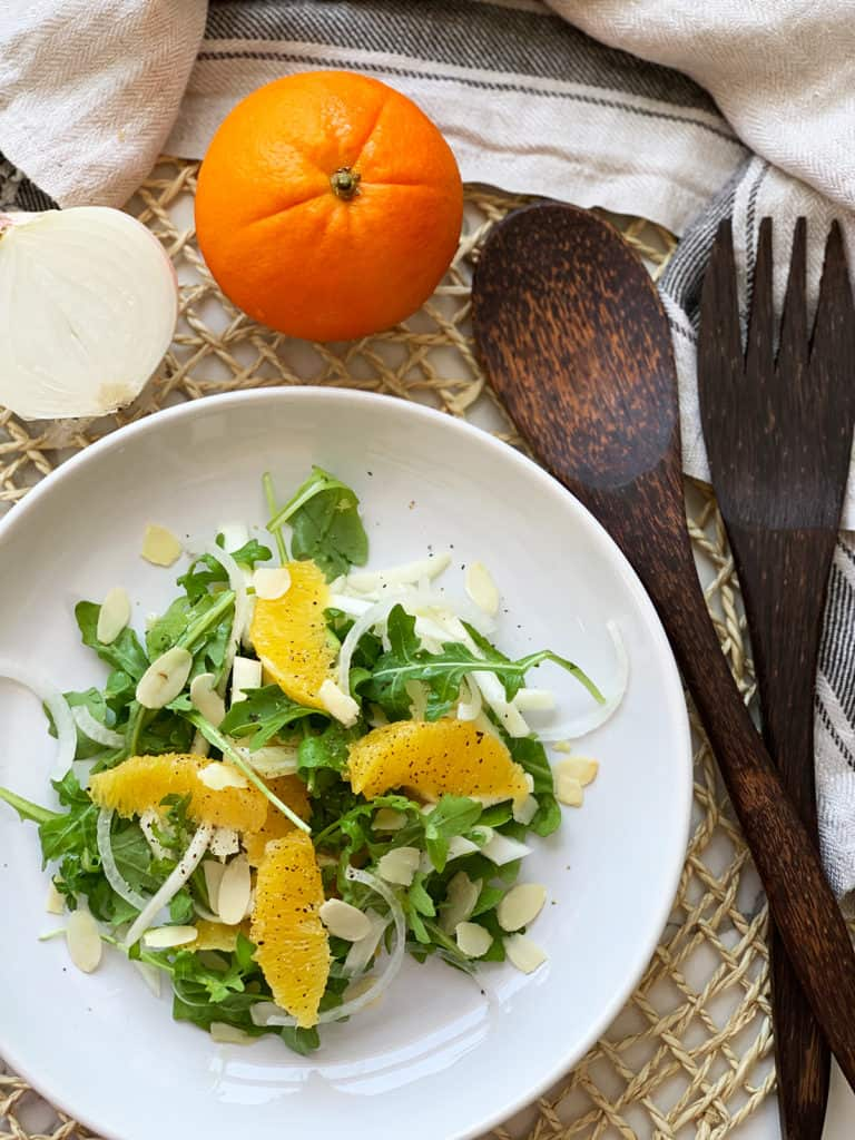 Orange and Fennel Salad (vegan recipe) served on a white plate with an orange, half onion and salad serving utensils in background