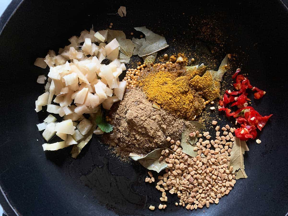 Curry leaves, ginger, mustard seeds, fenugreek, chilli, curry, turmeric in a pan ready to be fried to make yellow split pea dal, a vegan recipe by Plant Based Folk