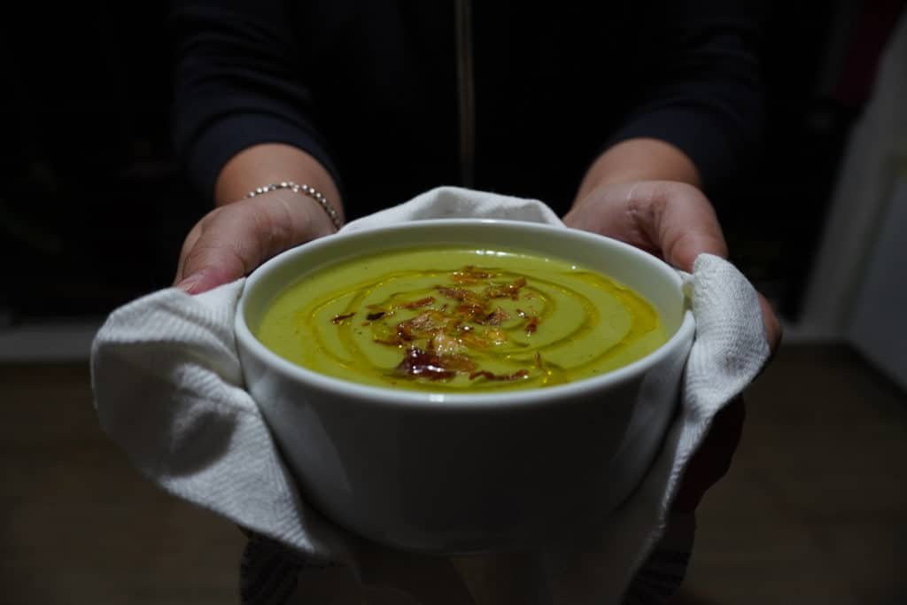 Vegan broccoli soup in a white bowl held by two hands