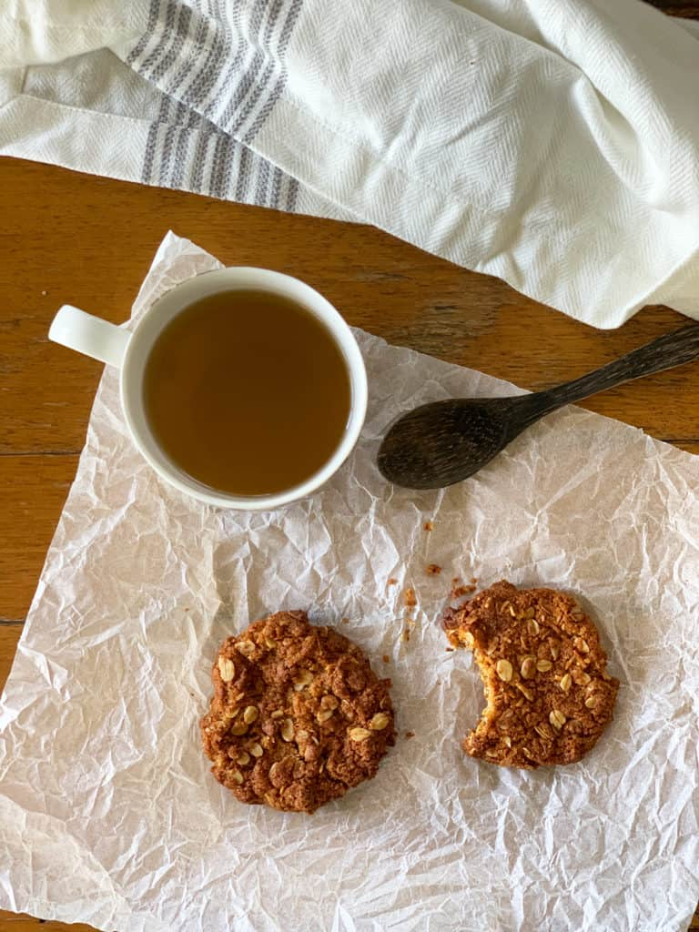 Two ANZAC biscuits one with a bite out of it with a cup of ginger lemongrass tea