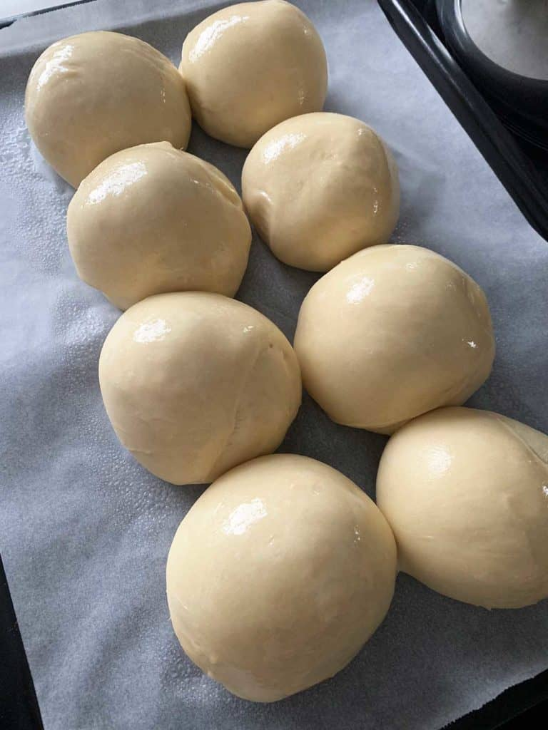 Dough balls coated in coconut oil ready to bake into dinner rolls