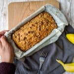 banana bread in a tin held by a hand