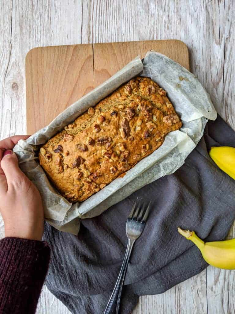 vegan aquafaba banana bread in a tin with hands holding it