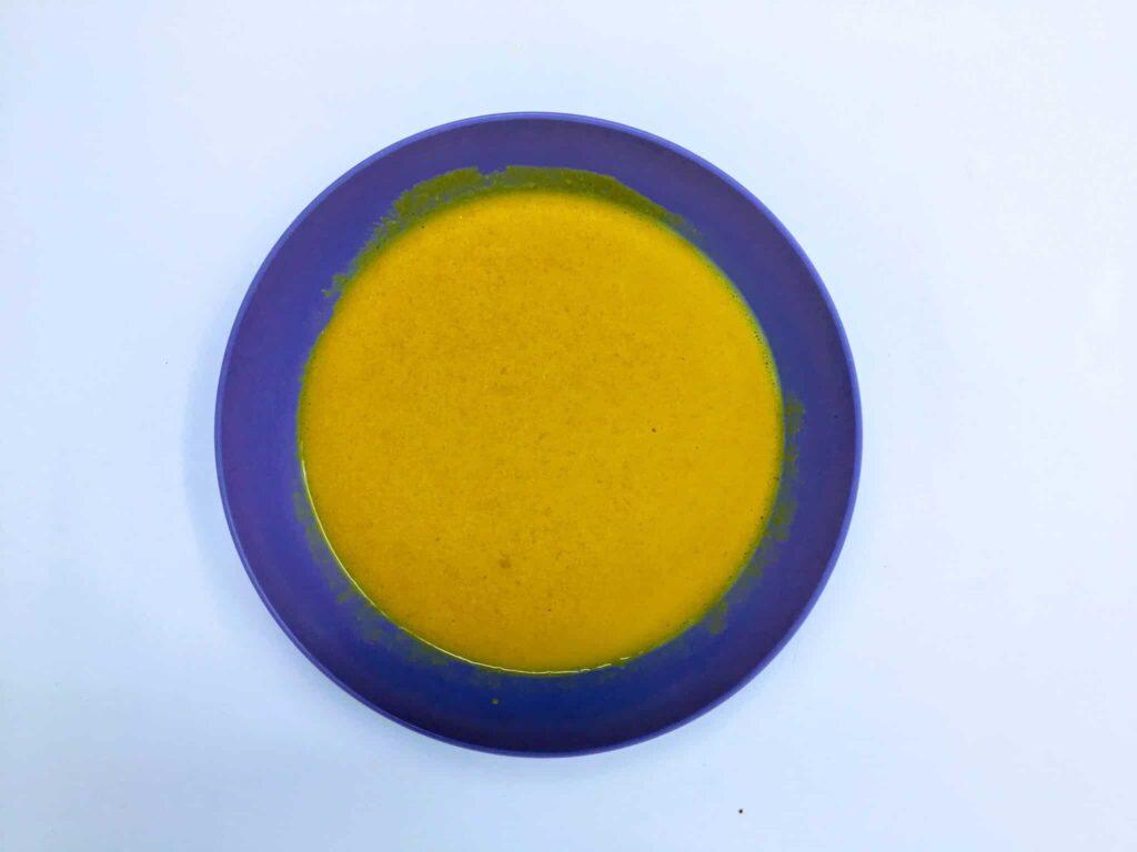 a vegan mustard dressing using aquafaba in a blue bowl