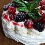 vegan pavlova covered in berries and mint garnish