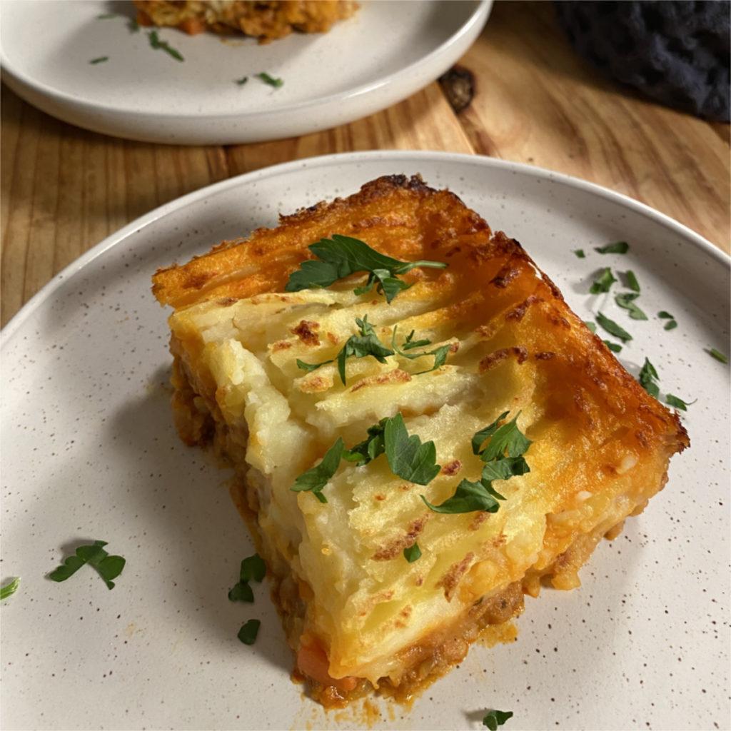 Slice of vegan shepherd's pie on a white plate