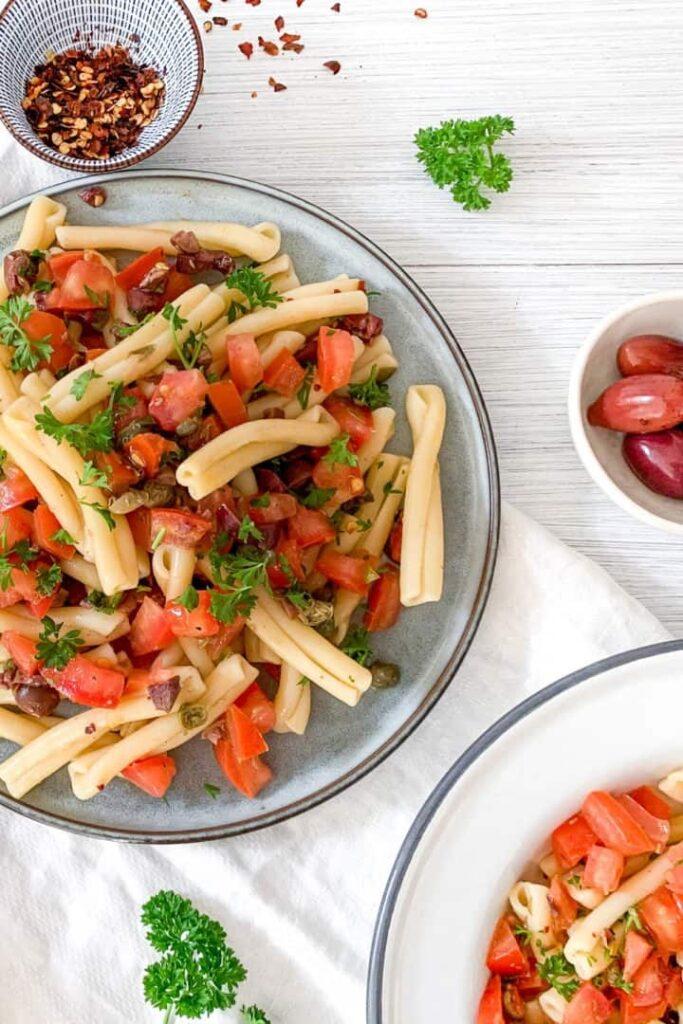 vegan puttanesca salad in a light blue bowl