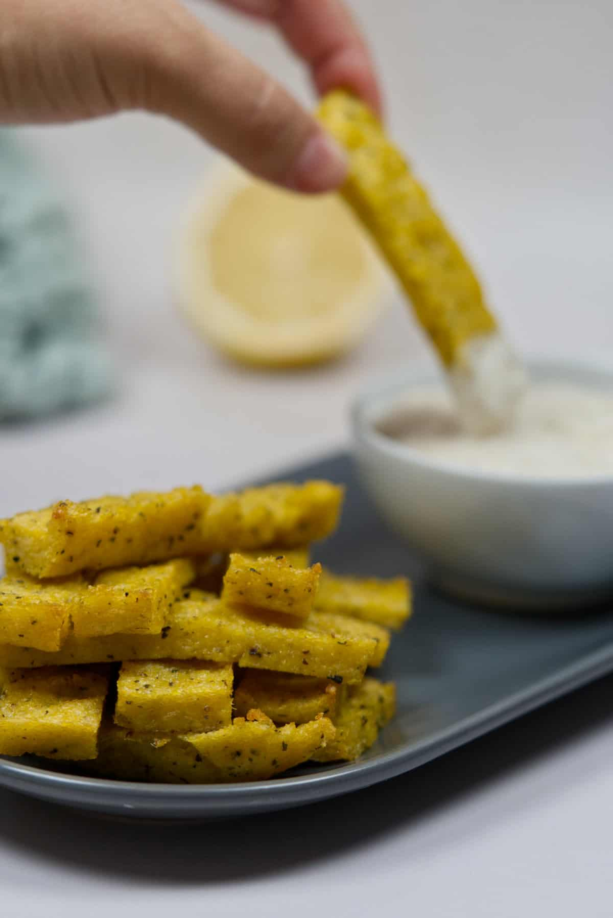 air fried polenta in a bowl with one being dipped into eggless mayonnaise in the background