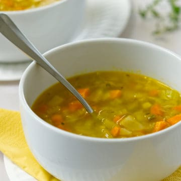 carrot and celery soup in a white bowl side view