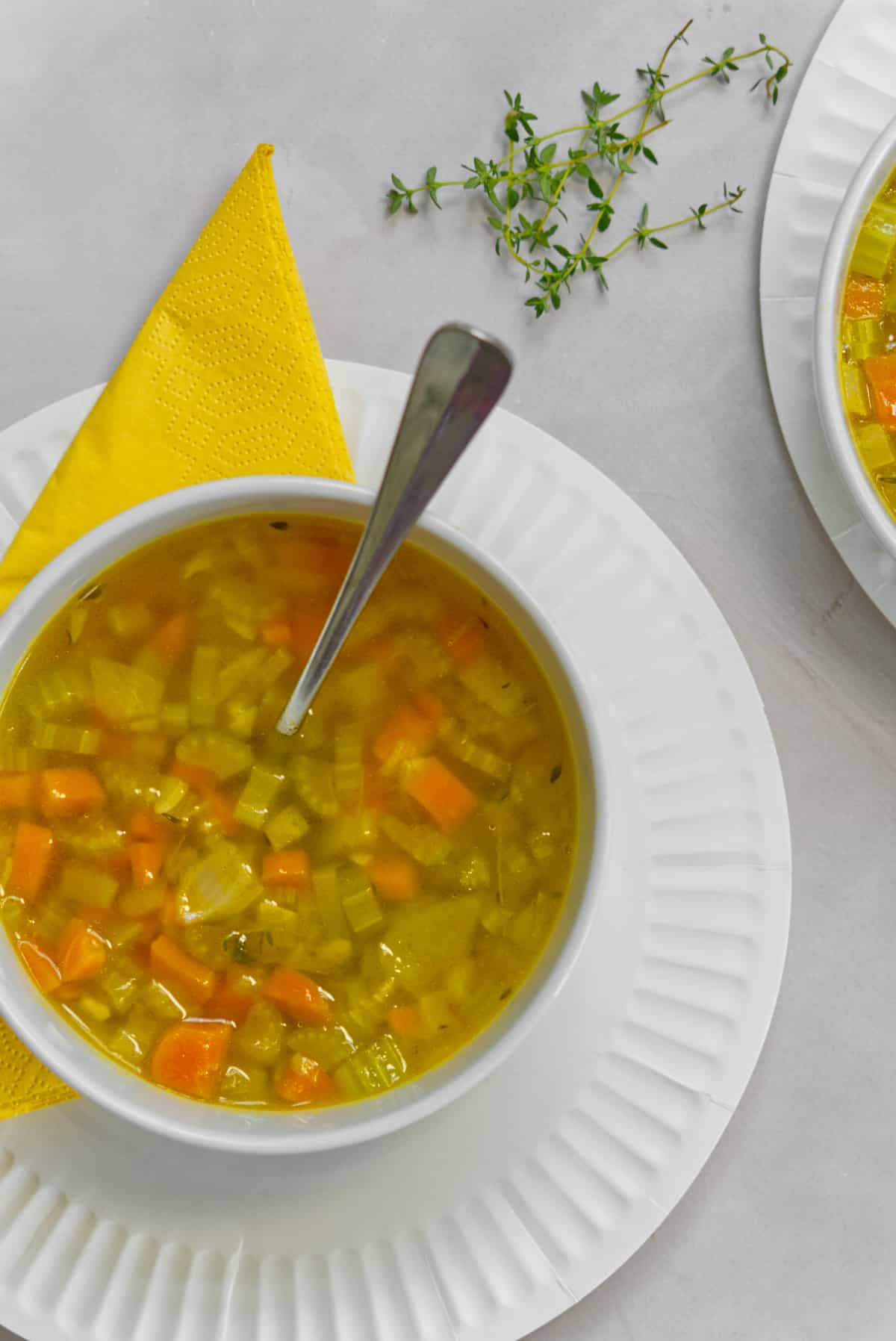 carrot and celery soup in a white bowl top down view