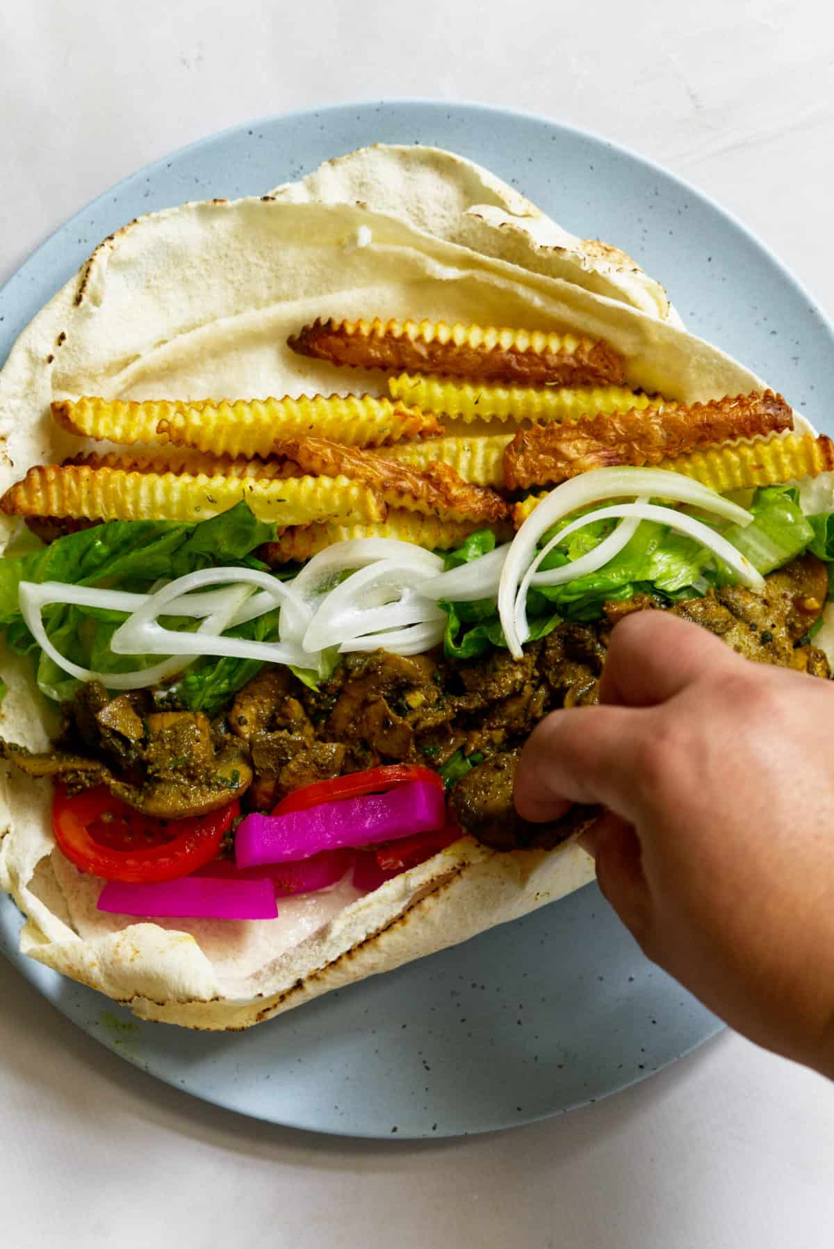 Vegan shawarma roll with a hand