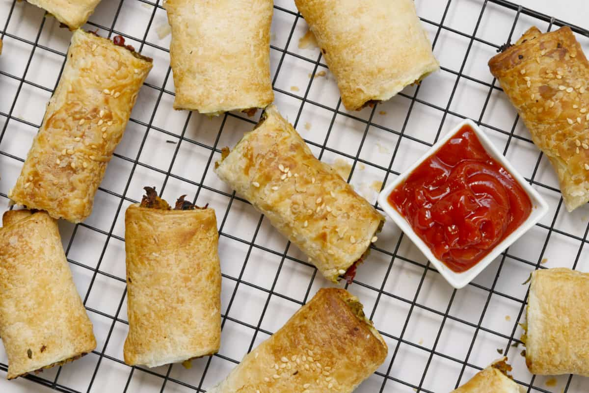 top down view of vegan sausage rolls on a wire rack with a bowl of tomato sauce