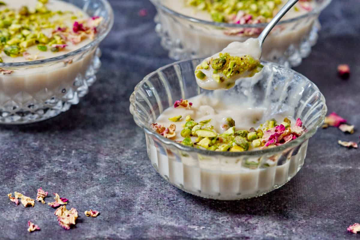muhallabi in a bowl with pistachio and rose petal garnish