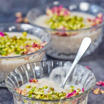 Muhallabi in three bowls with pistachio and rose petal garnish