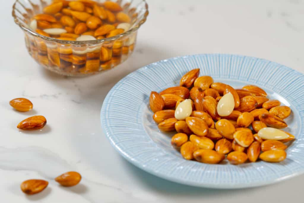 Almonds soaked in water and on a blue plate