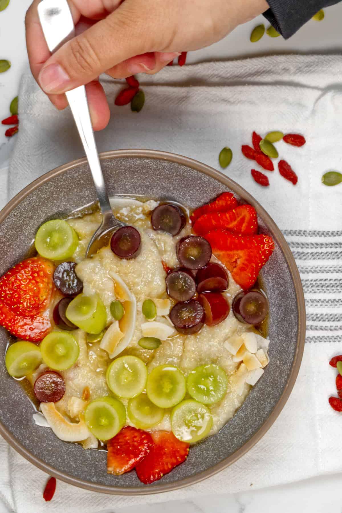 quinoa flakes porridge in a bowl being spooned