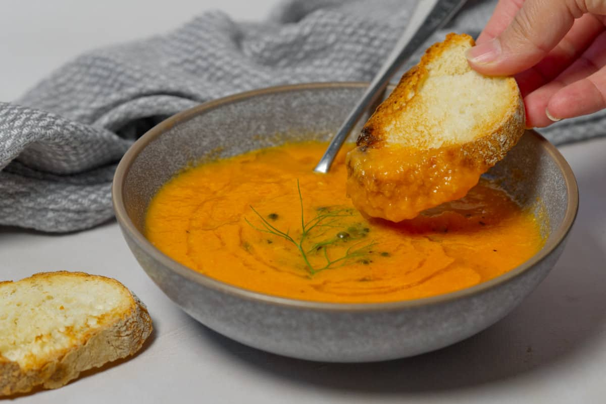 dunking bread into tomato soup
