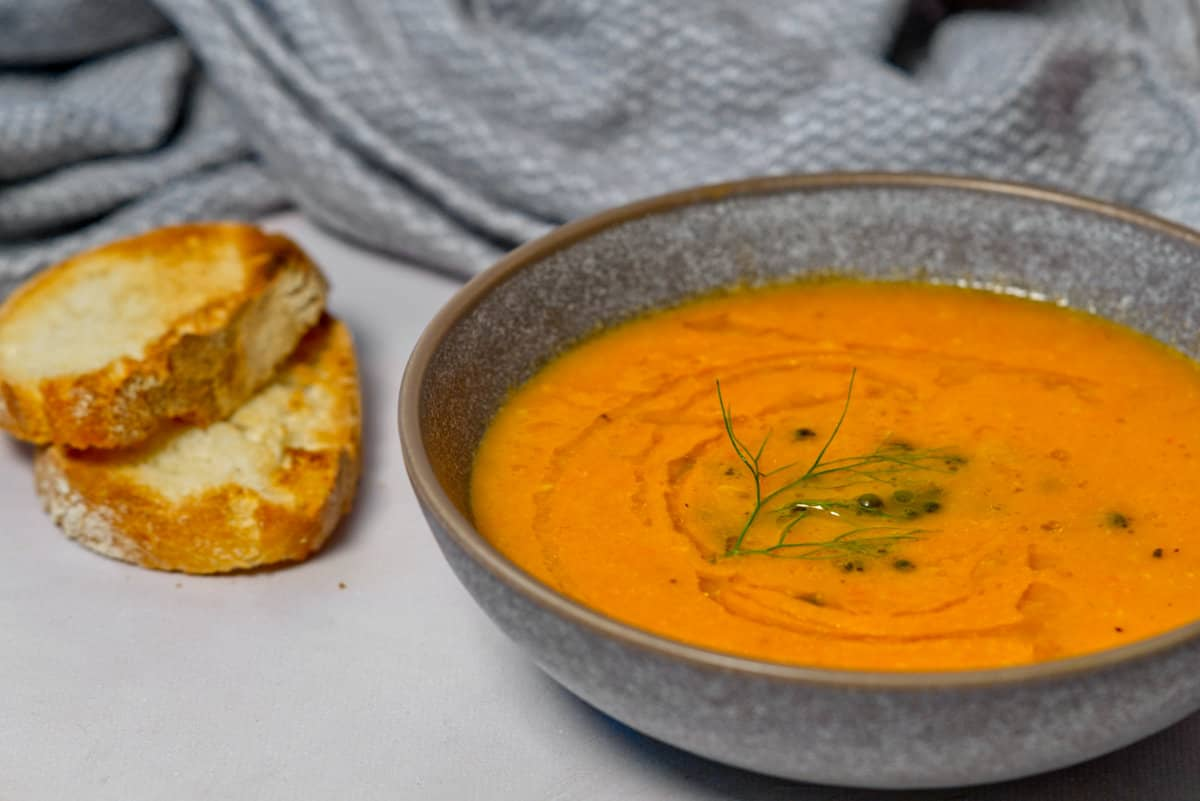 vegan tomato soup in a bowl with bread on the side