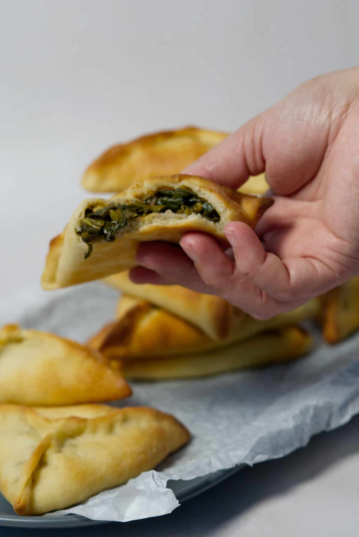 lebanese spinach pie held in a hand