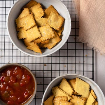 two bowls of gluten free crackers with salsa on the side