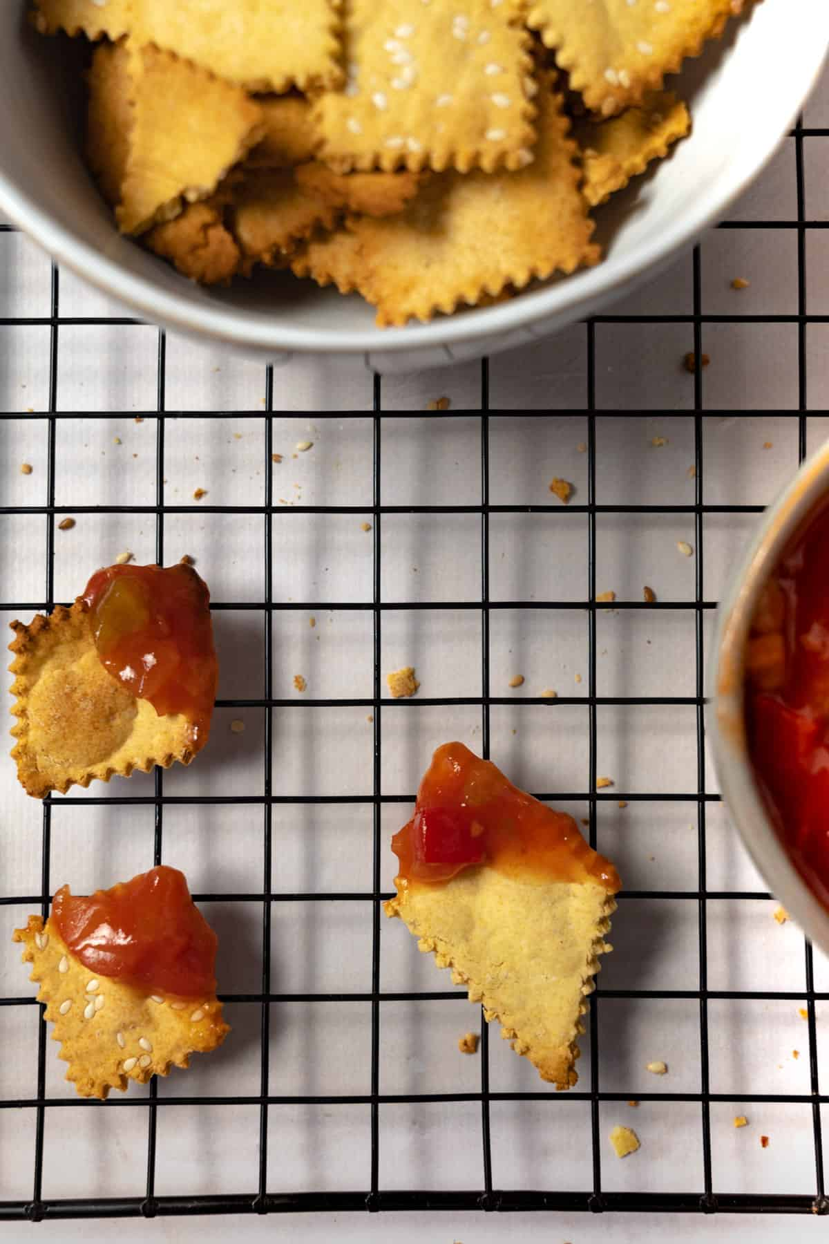 3 crackers dipped in salsa on a cooling rack