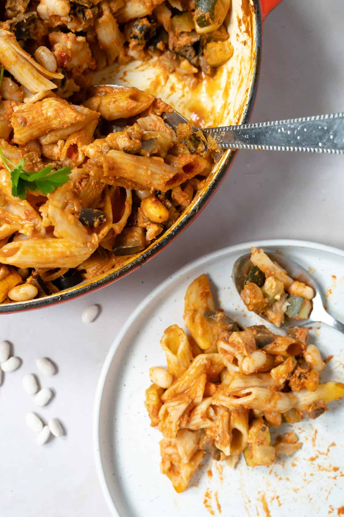 vegan baked pasta in a casserole dish and white plate