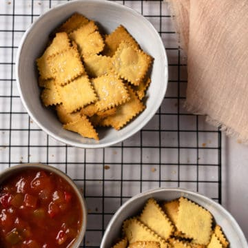 gluten free crackers in a white bowl with a side of salsa