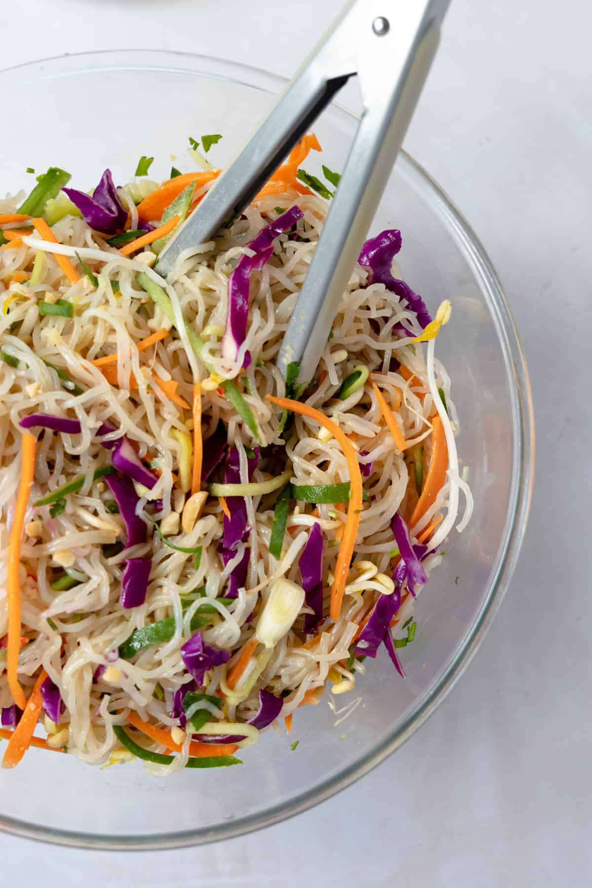 cold glass noodle salad in a bowl with tongs