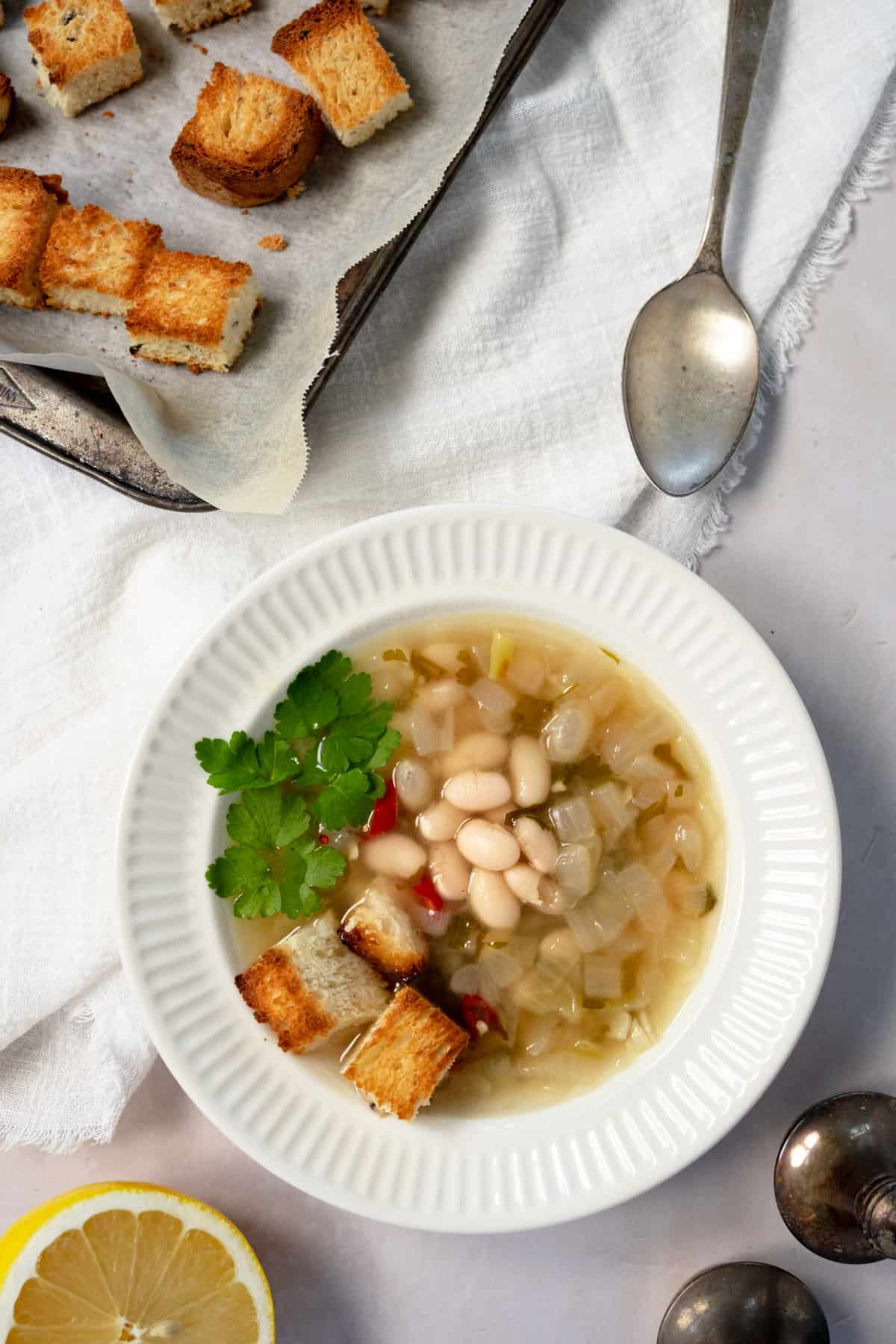 a white bowl of white bean soup with a side tray of croutons