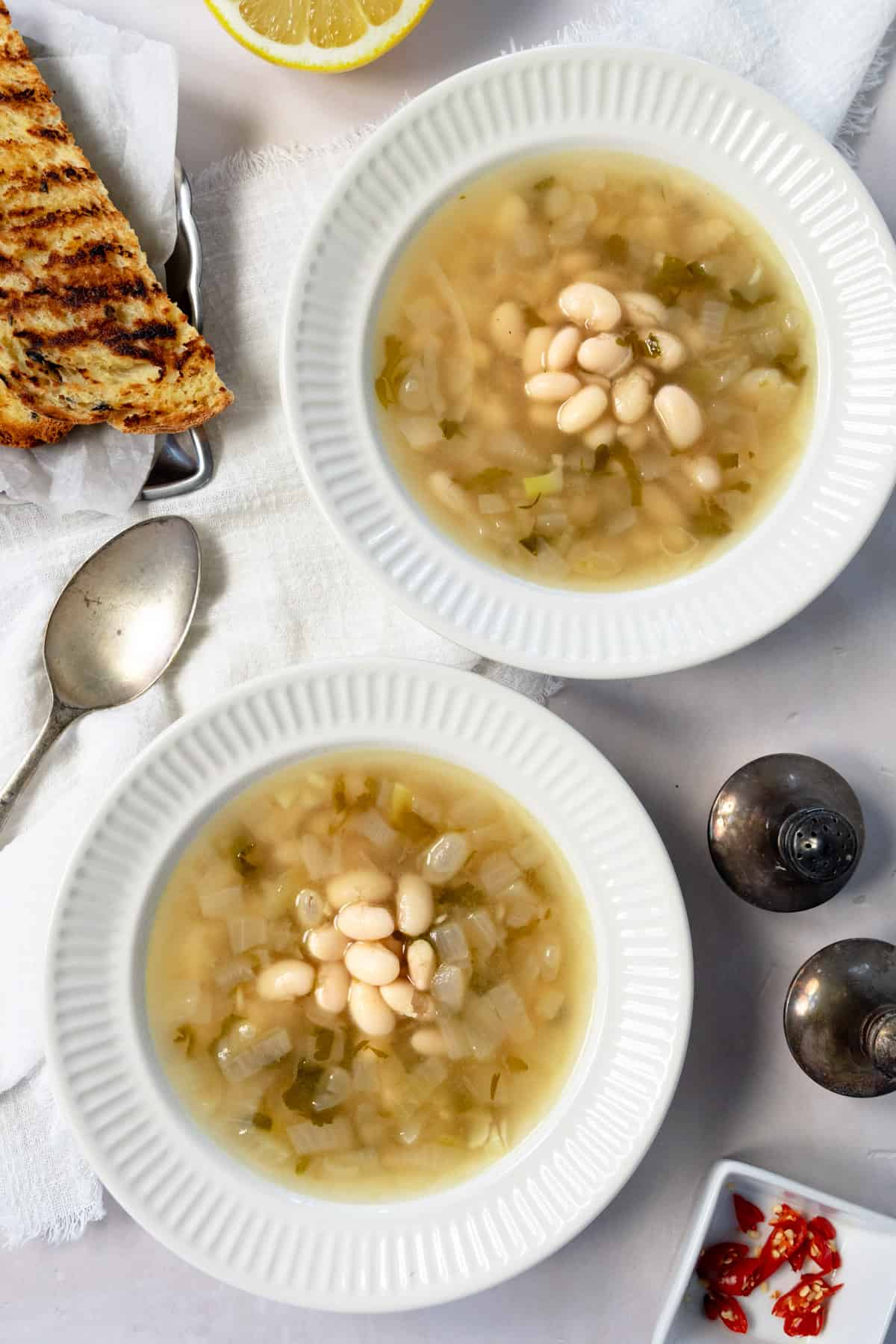 two white bowls of vegan white bean soup