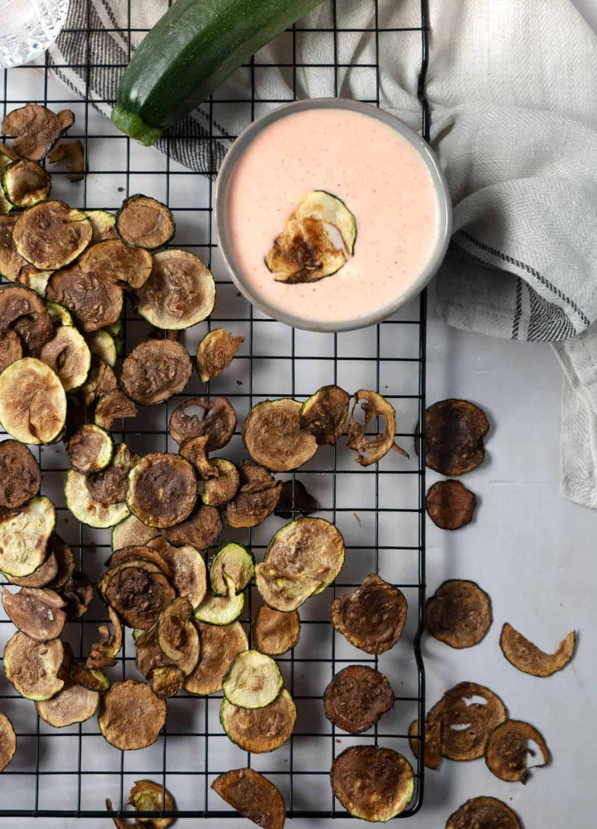 zucchini chips laid out on a wire rack with a pink dipping sauce on the side