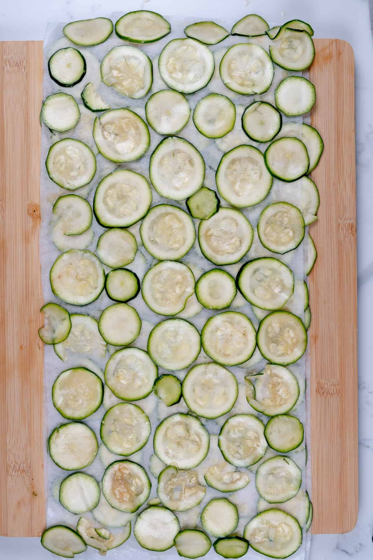 freshly cut and marinated zucchini coins laid out on paper towel