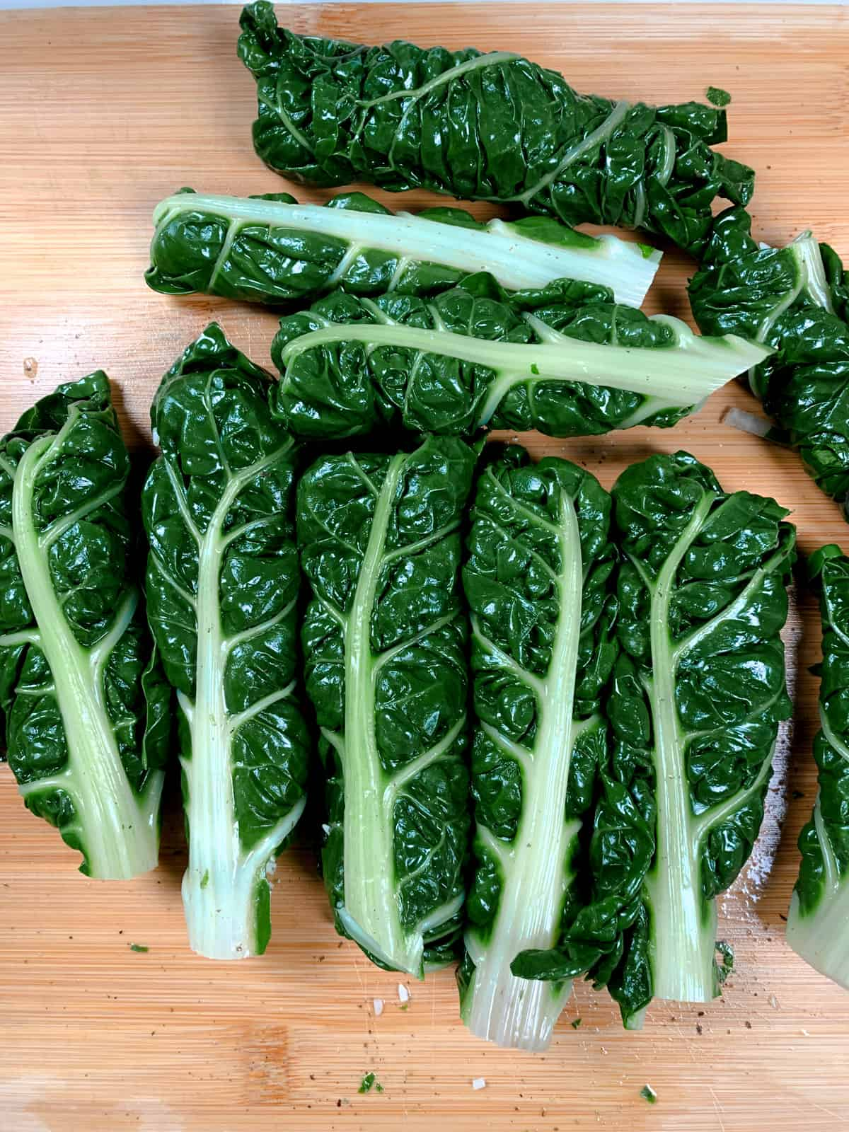 freshly rolled silverbeet leaves on a chopping board