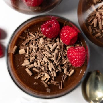 top down view of chocolate pudding with chocolate shavings and raspberries